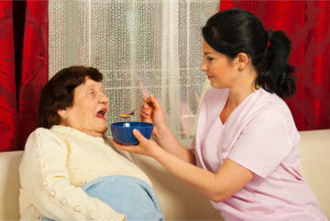 caregiver feeding senior woman