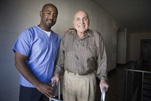 nurse and senior man walking