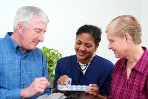 caregiver reminding senior couple to take their medicine